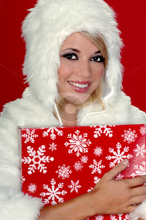 Fuzzy Snow Bunny stock photo, Sexy blond snow bunny in a white furry coat and hat holding a Christmas present over a red background by Robert Deal