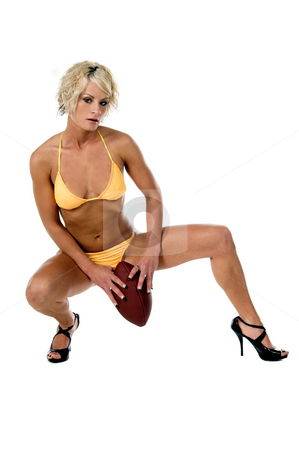 Bikini Blond Football stock photo, A beautiful blond woman wearing ayellow bikini and high heels squatted down with a football by Robert Deal
