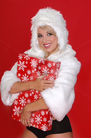 Fuzzy Snow Bunny stock photo, Sexy blond snow bunny in a white furry coat,  hat and black hot pants holding a Christmas present over a red background by Robert Deal