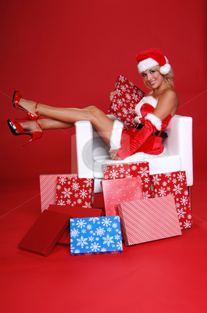 Santa's Helper stock photo, Sexy Mrs Santa Clauseholding a package and sitting in a snow white chair surrounded by Christmas gifts by Robert Deal