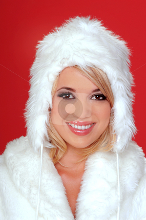 Wintery Snow Bunny stock photo, Sexy blond snow bunny in a white furry coat and hat and black hot pants over a red background by Robert Deal