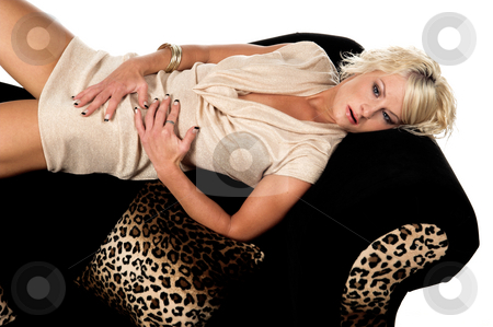 Pretty Blond Laying On Couch stock photo, Pretty blonde with short hair wearing a metallic tan cowel neck dress laying across the back of a black and lepoard print couch by Robert Deal