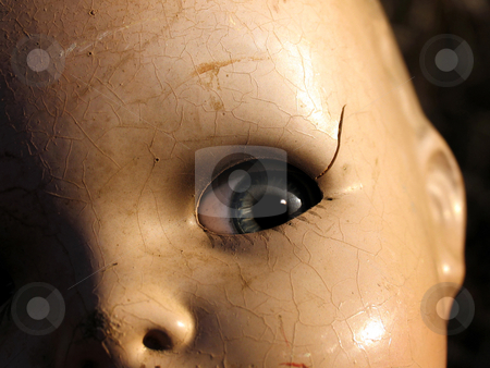 Antique doll close up stock photo, Antique doll face in strong lighting: cracks and dirt visible by Anita Peppers