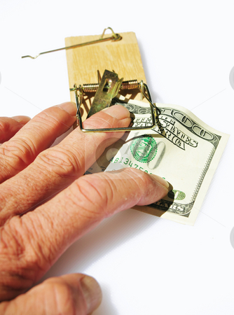 Trapped By Greed stock photo, A persons fingers caught in a mousetrap when taking a hundred dollar bill used for bait. by Lynn Bendickson
