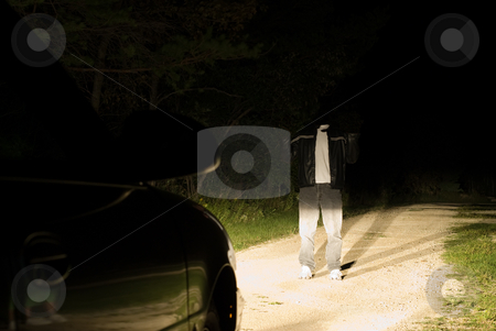 Headless Man stock photo, A headless man standing on a road, with car headlights on him by Richard Nelson