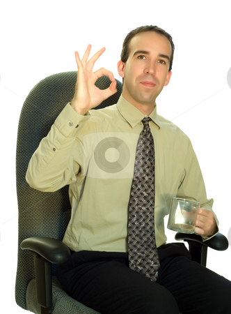 Businessman Sitting With Coffee stock photo, A young businessman sitting in a chair, holding his coffee and giving the sign for perfect with his hand by Richard Nelson