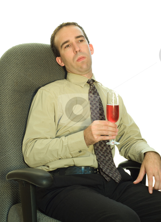 Work Celebration stock photo, A young businessman looking bored, while he sits in his chair drinking wine by Richard Nelson