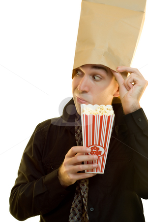 Snack Time stock photo, A businessman trying to hide while he eats his popcorn by Richard Nelson