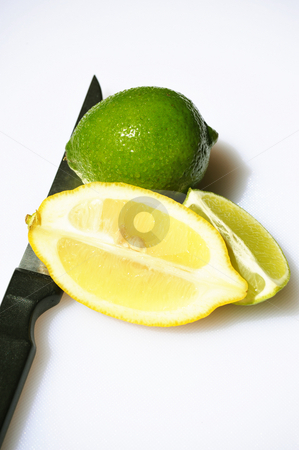 Lime And Sliced Lemon stock photo, Fresh Lime and sliced Lemon on a light background with a knife. by Lynn Bendickson