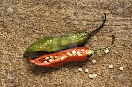Two chili peppers on a cutting table stock photo, Two chili peppers on a cutting table. by Pablo Caridad