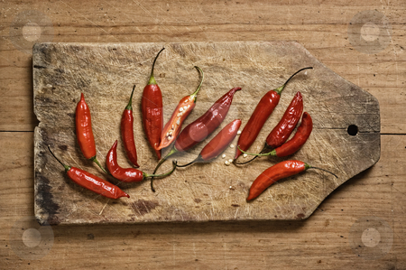 Red chili peppers on a cutting table. stock photo, Red chili peppers on a cutting table. by Pablo Caridad