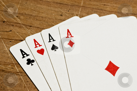 Four aces over an old wooden table stock photo, Four aces over an old wooden table, close up. by Pablo Caridad