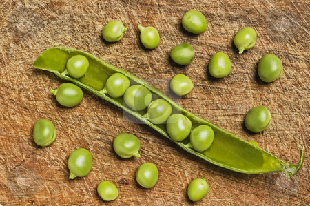 Fresh green peas on wooden background stock photo, Fresh green peas on wooden background, studio shot. by Pablo Caridad