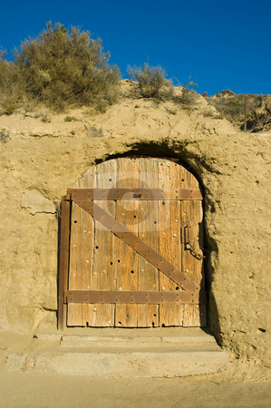 Antique door of a house carved in a cliff. stock photo, Antique door of a house carved in a cliff in patagonia, argentina. by Pablo Caridad