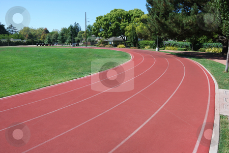 Athletic Track stock photo, Athletic Track Curving Around Green Grass Field by Denis Radovanovic