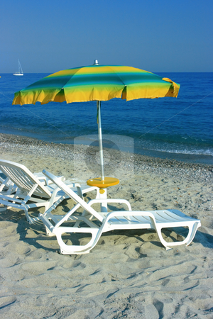 Colorful parasol stock photo, Colorful parasol over two chaise-longues on a beach by Natalia Macheda