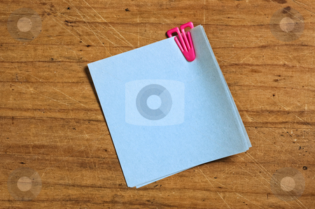 Note with plastic clip  stock photo, Post it with plastic clip on wooden board. by Pablo Caridad