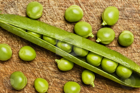 Fresh green peas stock photo, Fresh green peas on wooden background, studio shot. by Pablo Caridad
