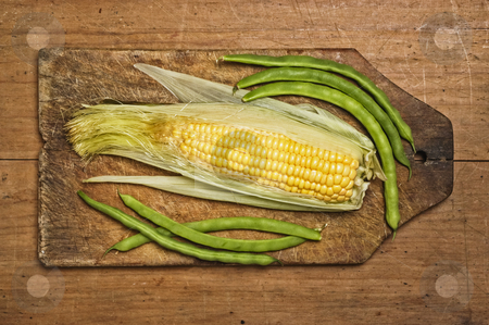 Green beans and corn  stock photo, Green beans and corn on wooden table by Pablo Caridad