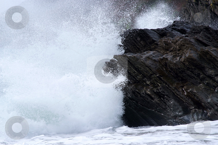 Contrast stock photo, The sea crashing against dark tough rocks by Paul Phillips