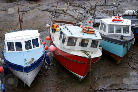 Low tide stock photo, Three fishing boats at low tide by Paul Phillips