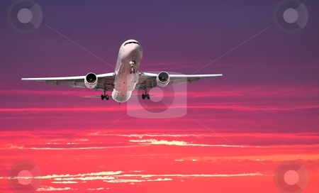 Large airliner arriving at sunset stock photo, Widebody jet airplane on approach with colorful dramatic sky in the background by Pierre Landry