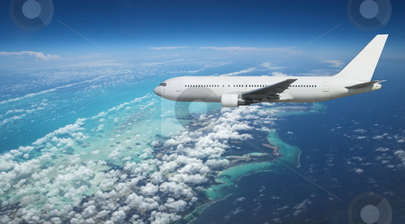 Airliner over exotic island stock photo, Large jet airplane arriving over exotic vacation destination by Pierre Landry