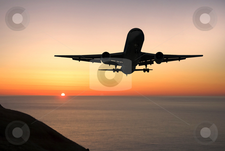 Airliner landing at sunrise stock photo, Large jet airplane approaching to land at sunrise by Pierre Landry