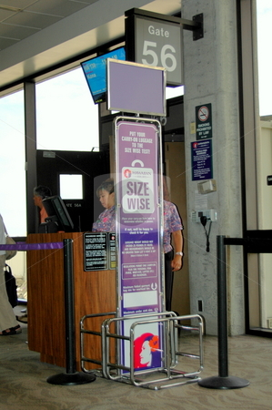 Airport lounge has a sign for checking your carry on luggage sizes. stock photo, Airport signage in a gate loung helps passengers determine if their carry on luggage is the correct size. Hawaii airport by Janie Mertz