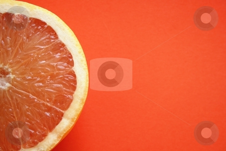 Grapefruit close-up on orange paper background stock photo,  by Gautier Willaume