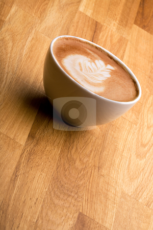 Cafe Latte stock photo, A cappuccino with latte art on a wooden table by Tyler Olson