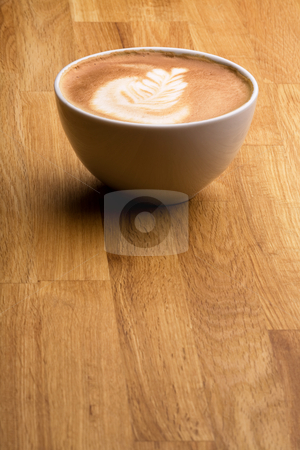 Fancy Coffee stock photo, A cappuccino with latte art on a wooden table by Tyler Olson