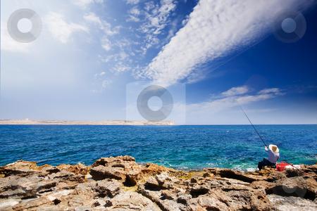 Fishing in Ocean stock photo, A maltese fisherman fishing in the sea by Tyler Olson