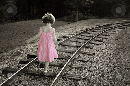 Pink dress stock photo, Colorized black and white with little girl in a pink dress walking on railroad track by Anita Peppers