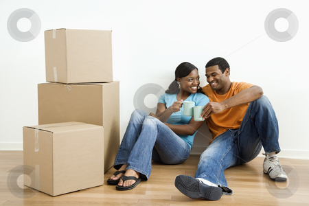 Portrait of couple with boxes. stock photo, African American male and female couple sitting on floor next to moving boxes relaxing. by Iofoto Images