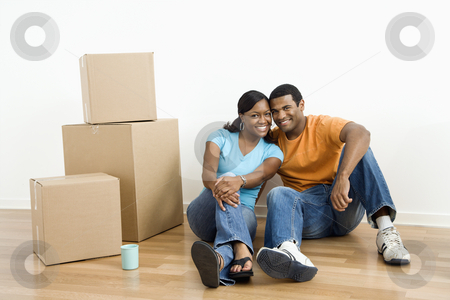 Portrait of couple with boxes. stock photo, African American male and female couple sitting on floor next to moving boxes. by Iofoto Images