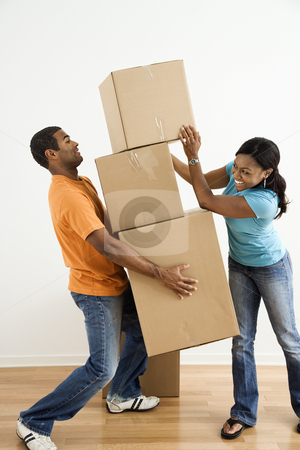 Couple with moving boxes. stock photo, African American female placing boxes on large stack man is holding. by Iofoto Images