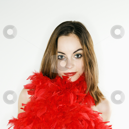 Woman with feathers. stock photo, Pretty  Caucasian  woman with red feather boa around body looking at viewer. by Iofoto Images