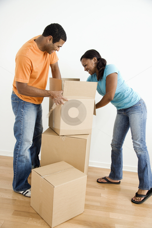 Couple packing boxes stock photo, African American male and female couple packing cardboard boxes. by Iofoto Images