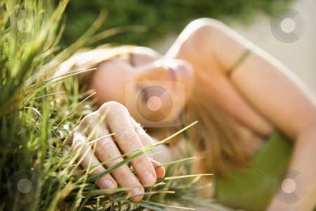 Woman in grass. stock photo, Selective focus portrait of young woman relaxing in grass. by Iofoto Images