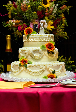 Wedding cake with flowers stock photo, A white wedding cake accompanied with a variety of flowers. The cake is sitting on a table with a fuchsia table cloth. by Paul Hakimata