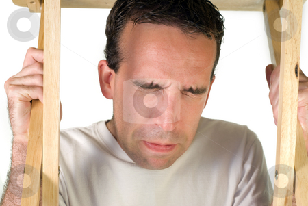 Terrified Man stock photo, A young man cringing under a table, isolated on a white background by Richard Nelson