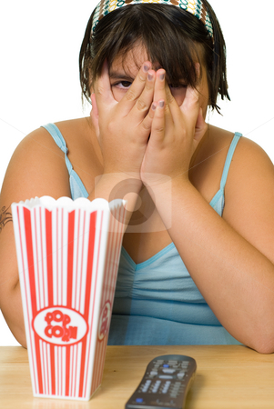 Girl Watching Scary Movie stock photo, A girl covering her face and watching a scary movie by Richard Nelson