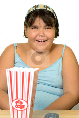 Girl eating popcorn stock photo, A girl with a box of popcorn in front of her. by Richard Nelson