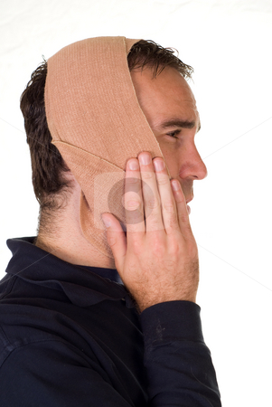 Toothache stock photo, Profile view of a man weaing a bandage for his tooth pain by Richard Nelson