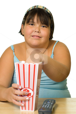Girl Watching Movie stock photo, A young girl watching a movie and eating popcorn by Richard Nelson