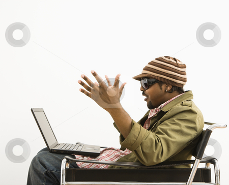 Surprised man with laptop. stock photo, Side view of African-American mid-adult man wearing hat and making surprised expression at laptop computer. by Iofoto Images