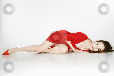 Pretty woman lying down. stock photo, Attractive Caucasian  woman wearing red dress lying on floor looking at viewer. by Iofoto Images