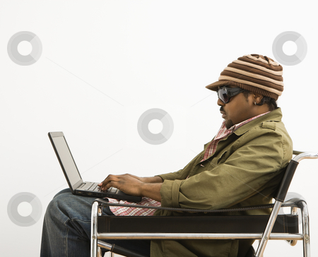 Man on laptop. stock photo, Side view of African-American mid-adult man wearing hat and typing on laptop computer. by Iofoto Images