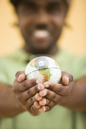 Man holding globe. stock photo, African-American mid-adult man wearing hat holding small globe toviewer. by Iofoto Images